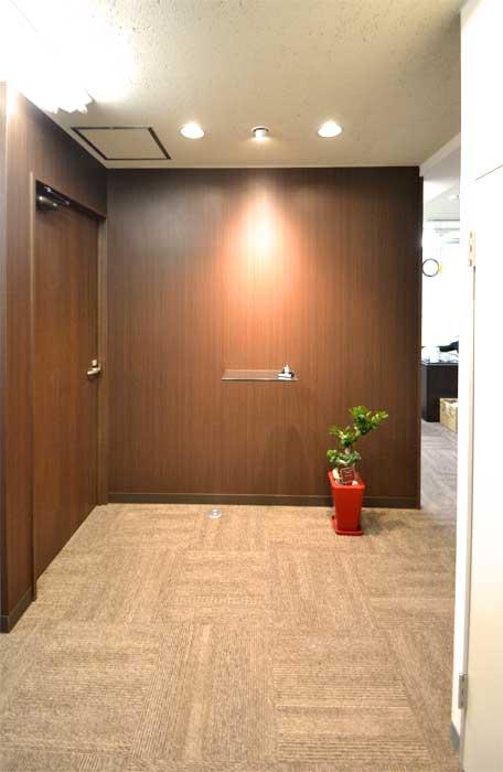 カーペットと木目調壁紙が醸し出す落ち着きあるオフィスのデザイン事例