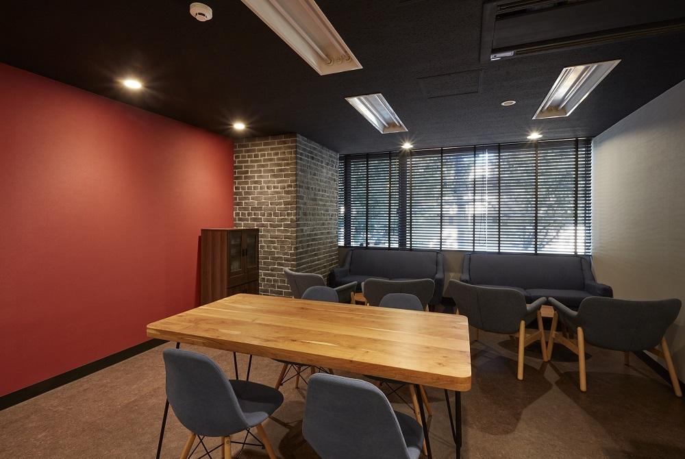 コーポレートカラーの赤・黒が映えるシャープなオフィスデザイン事例